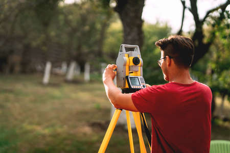 Portrait of professional surveyor engineer measuring and working with total station