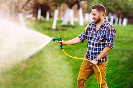 backyard gardening details - portrait of gardener using water hose and watering the lawn, grass and plants. Stock fotó