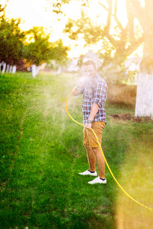 Garden maintainance- man playing with hose and watering the lawn