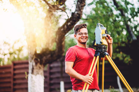 Portrait of surveyor engineer working with total station on garden elevation