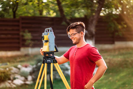Portrait of surveyor engineer using equipment with theodolite and total station at a construction site