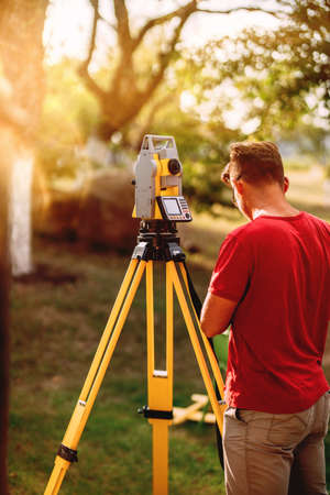portrait of surveyor caucasian engineer working with total station theodolite at landscaping project