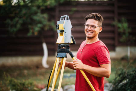 Details of survey engineer using and working with total station theodolite at landscaping project Stock Photo