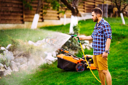 Close up of smiling man watering backyard lawn using hose. Irrigation systems Stock fotó