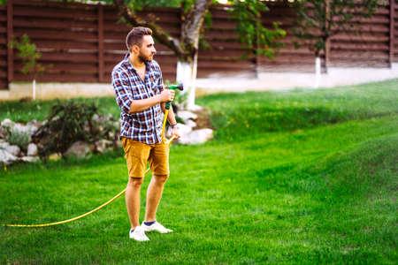 cheerful man, caucasian male watering home garden