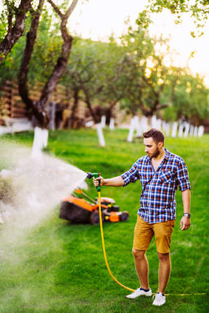 man with water hose watering the grass, watering the lawn during summer evening Stock fotó