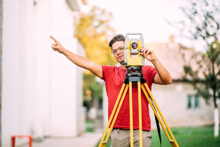 cartographer engineer, surveyor working with total station construction site elevation