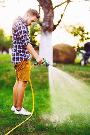Professional gardener working in garden, using hose and watering plants