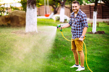 Professional gardener smiling working in garden, using hose and watering lawn and grass