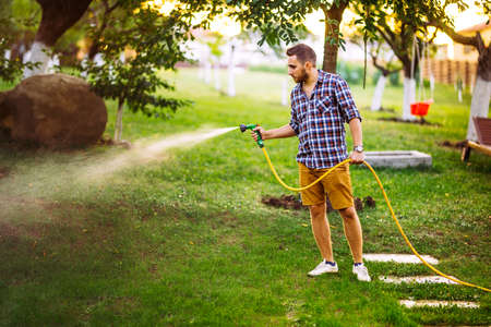 backyard gardening - portrait of gardener using water hose and watering the lawn, grass and plants.