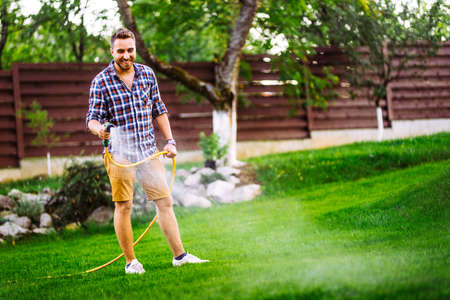 Garden maintainance- smiling man, happy man with hose and watering the lawn Stock fotó