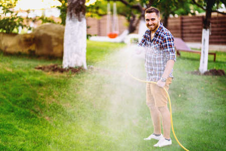 Gardening details - man working with hose and watering the lawn