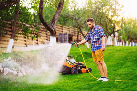 Portrait of caucasian man watering lawn in backyard using hose and water Stock fotó