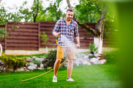 Caucasian man working on grass irrigation. Hose manual system, watering the lawn