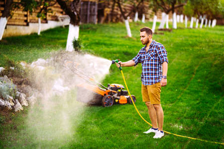 man with water hose watering the grass, watering the lawn during summer season Stock fotó