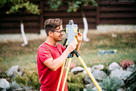surveyor engineering equipment with theodolite and total station in a garden at a construction site Stock Photo