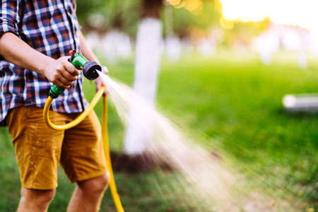 Gardening and maintainance- close up of man hands with hose watering the lawn