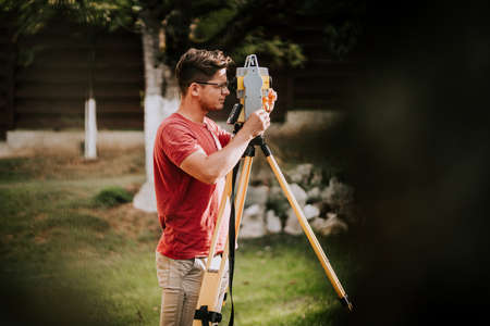 Portrait of surveyor engineer working with total station theodolite and gps system on construction site