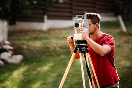 portrait of smiling surveyor working with total station with coordinates, cartography industry details