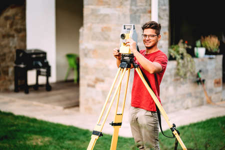 Surveyor engineer working with total station theodolite at landscaping project