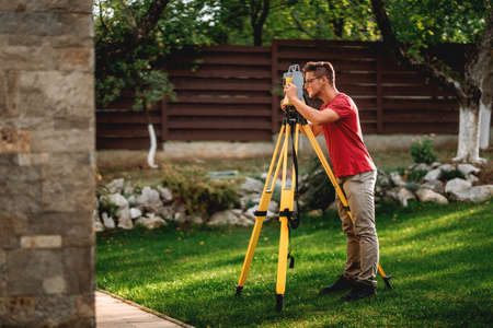portrait of professional surveyor working with total station theodolite on landscaping project