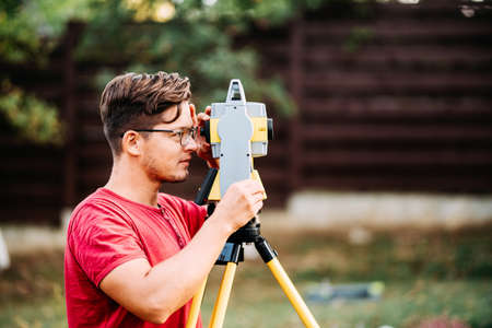 surveyor engineering working with equipment and theodolite, total station at a construction site Stock Photo