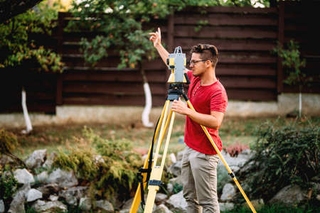 survey engineer in garden elevation construction site using and working with theodolite