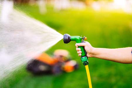 close up of gardener hands working in garden, using hose and watering plants 写真素材