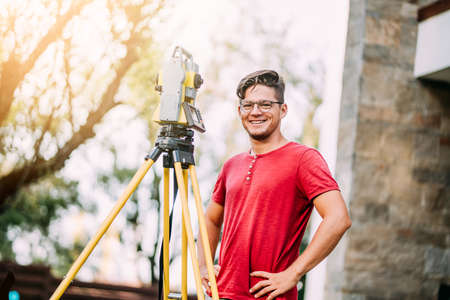 close up portrait of survey engineer using and working with total station theodolite at landscaping project