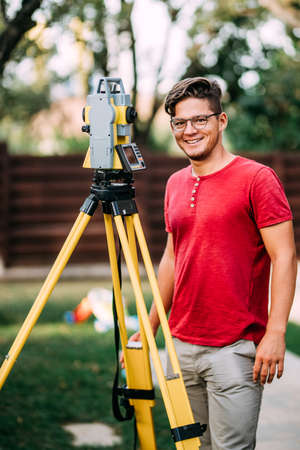 Gardening surveyor engineer working with total station on garden elevation during landscaping