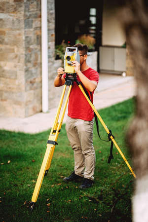 landscaping details - surveyor engineer in garden elevation working with total station theodolite