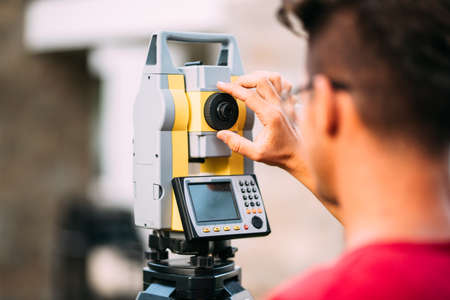 close up details of survey engineer using and working with total station theodolite at landscaping project