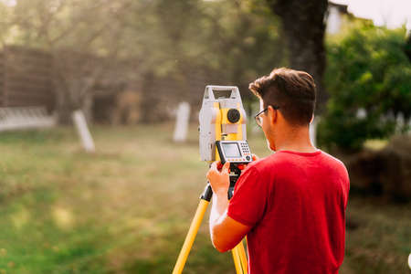 Professional surveyor engineer measuring and working with total station Stock Photo