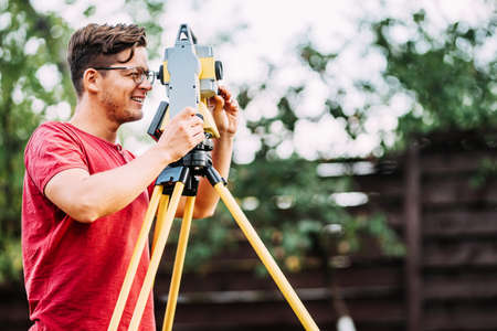 Portrait of smiling surveyor working with total station in garden