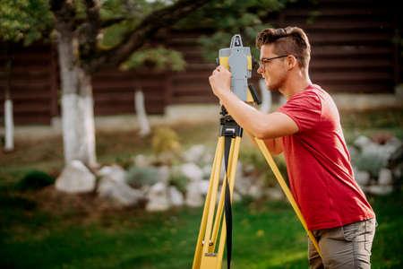 Portrait of surveyor engineer using professional total station