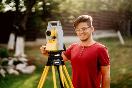 portrait of surveyor caucasian engineer working with total station at landscaping project