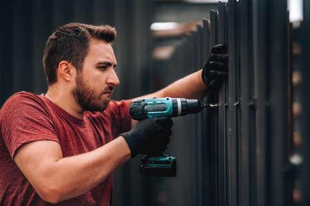 Retrato de trabajador de la construcción instalando elementos metálicos con destornillador inalámbrico