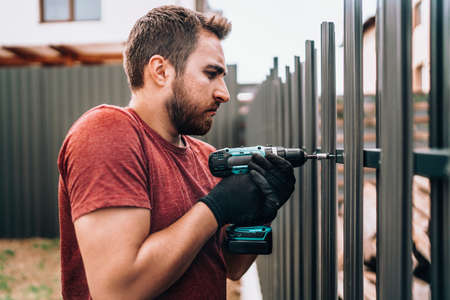 Construction worker using electrical screwdriver and mounting metal elements on fence