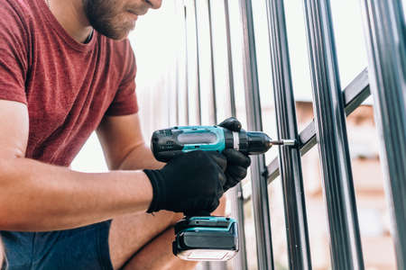 Worker with cordless screwdriver power tool fastening screws