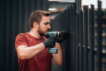 Caucasian construction man working with screwdriver on metal fence