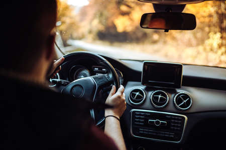 Portrait of mid caucasian adult driving a car through forest on asphalt road. Man going for a drive Stock Photo
