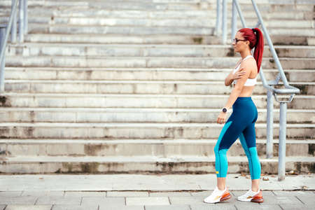 Attractive woman in sportswear exercising outdoors. Portrait of woman resting and running during cardio training