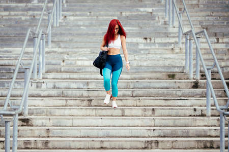 Woman preparing for training on stadium stairs. Portrait of professional athlete working out Stock Photo