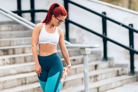 Portrait of determined sportswoman doing stretching workout on running routine