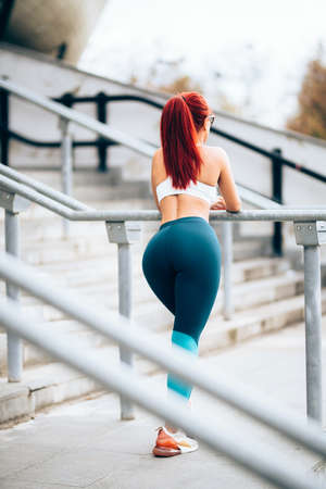 Female runner stretching and doing squats after jogging training. Fitness concept on stadium