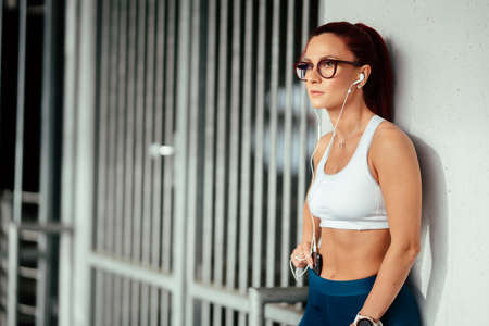 Portrait of athletic fitness girl resting  after workout and stretching while listening to music