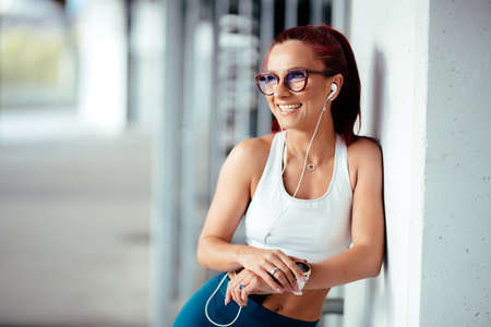 Woman listening to music, doing workout exercises on concrete background. Portrait of woman in sports clothing using smartwatch and listening to music on smartphone Stock Photo