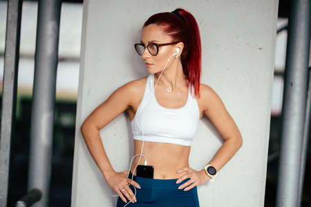 woman in sports clothing listening to music on smartphone., doing workout exercises