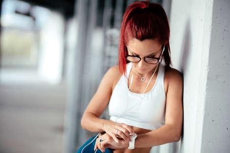 Portrait of woman in sports clothing using smartwatch and listening to music on smartphone