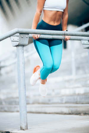 Close up details of fitness young woman stretching outdoors and training, doing exercises. Training and working out sportswoman concept Stock Photo